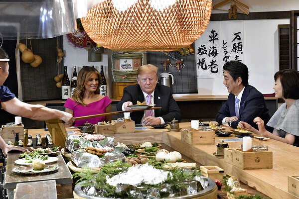 President Donald Trump takes a dish from a chef at a robatayaki charcoal grill restaurant in Tokyo on Sunday as, from left, first lady Melania Trump, Prime Minister Shinzo Abe and his wife, Akie, look on.
