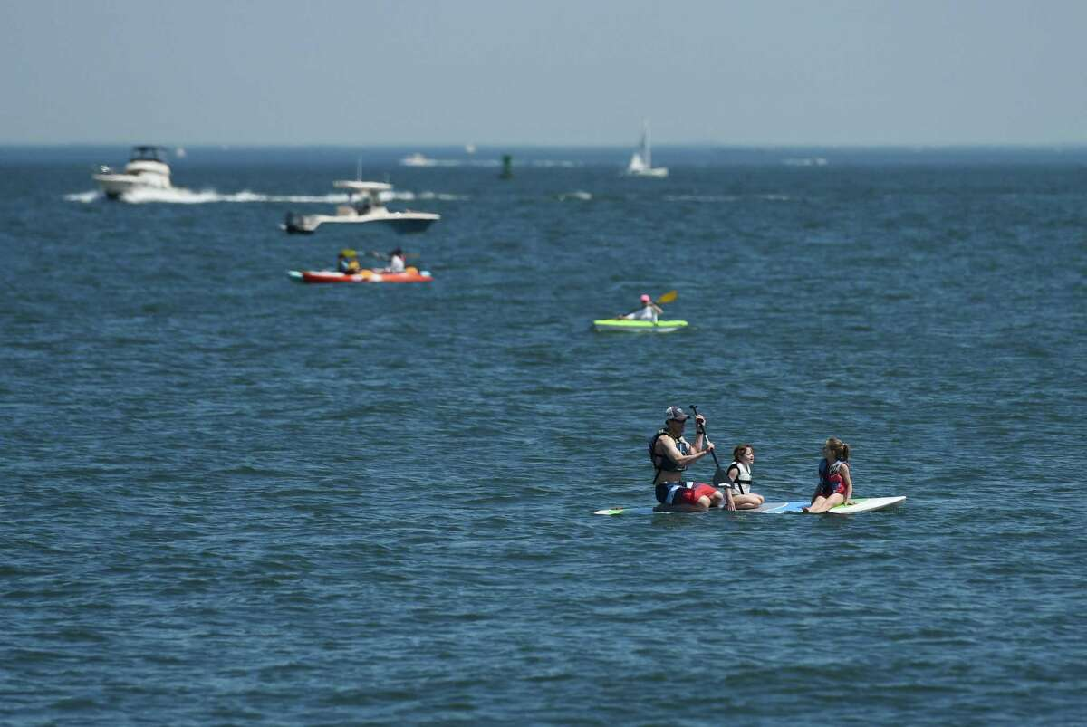 Paddleboarders and kayakers use the water in Stamford Harbor.