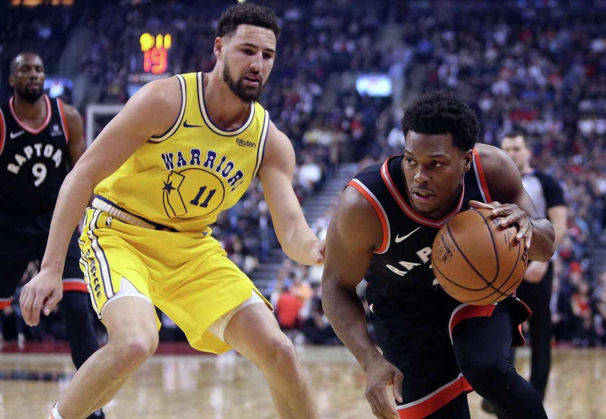 TORONTO, ON - NOVEMBER 29: Kyle Lowry #7 of the Toronto Raptors dribbles the ball as Klay Thompson #11 of the Golden State Warriors defends during the first half of an NBA game at Scotiabank Arena on November 29, 2018 in Toronto, Canada.