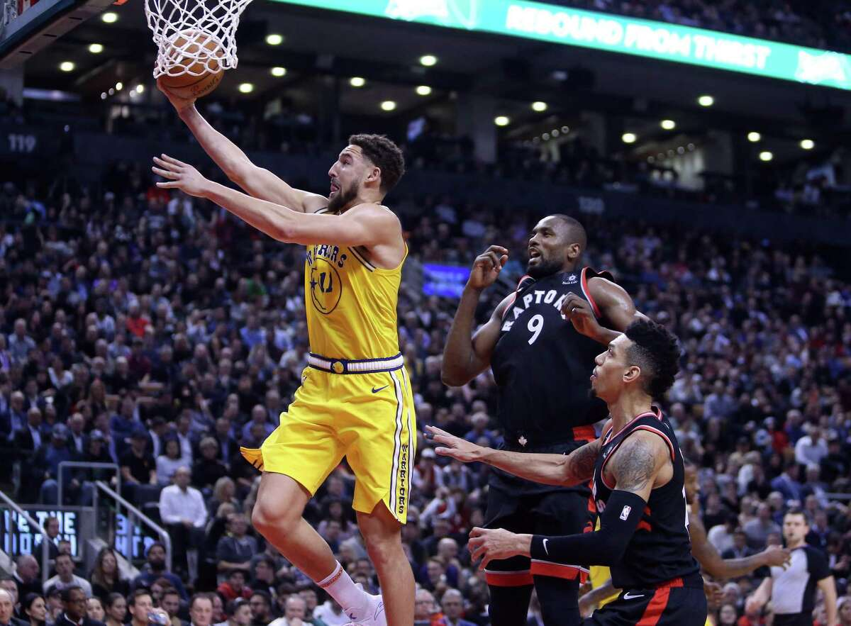 TORONTO, ON - NOVEMBER 29: Klay Thompson #11 of the Golden State Warriors shoots the ball as Serge Ibaka #9 and Danny Green #14 of the Toronto Raptors defend during the second half of an NBA game at Scotiabank Arena on November 29, 2018 in Toronto, Canada.