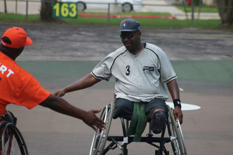 Chris Pettway receives congratulations from the Rollin' Astros shortstop after belting a solo homer over the 163-foot sign in left field during Sunday's Wheelchair Wind-Up title game. Photo: Robert Avery