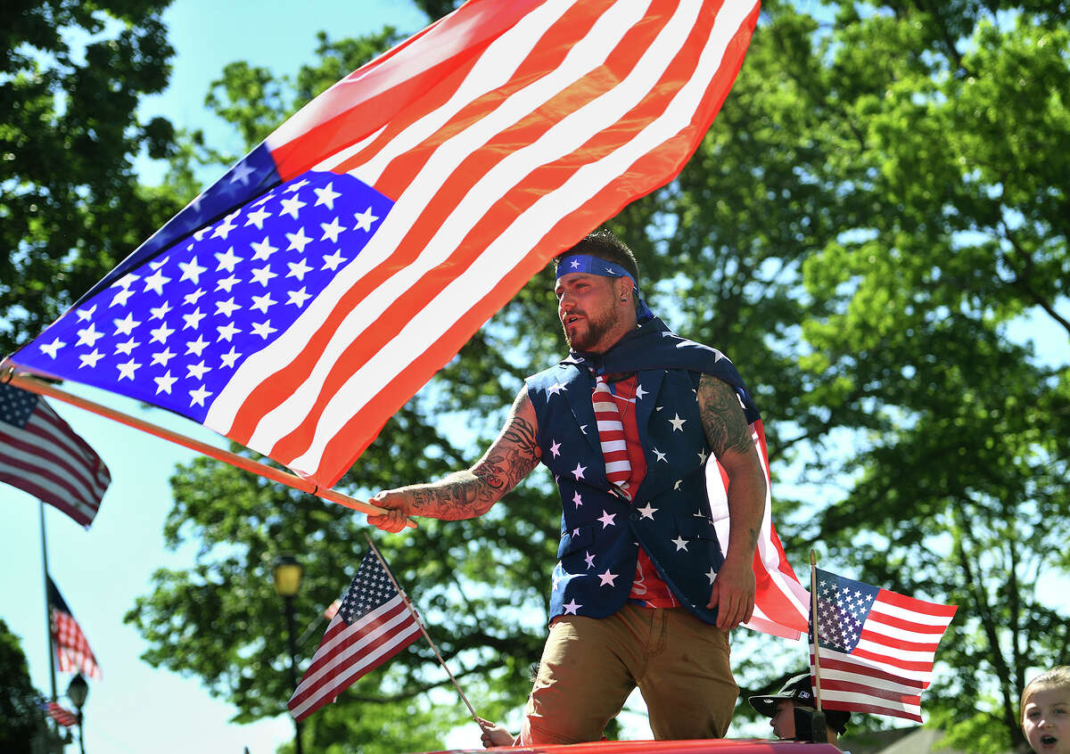 John DeCarlo waves a giant American flag from atop the Derby Little League float in the Derby Shelton Memorial Day Parade on Elizabeth Street in Derby, Conn. on Monday, May 27, 2019.