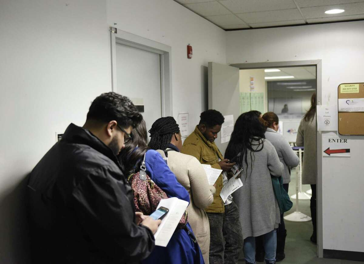 Last-minute voters wait in line to register to vote at the Stamford Government Center in Stamford, Conn. on Election Day, Tuesday, Nov. 6, 2018. The line for same-day registration at the Government Center was long throughout most of the day.