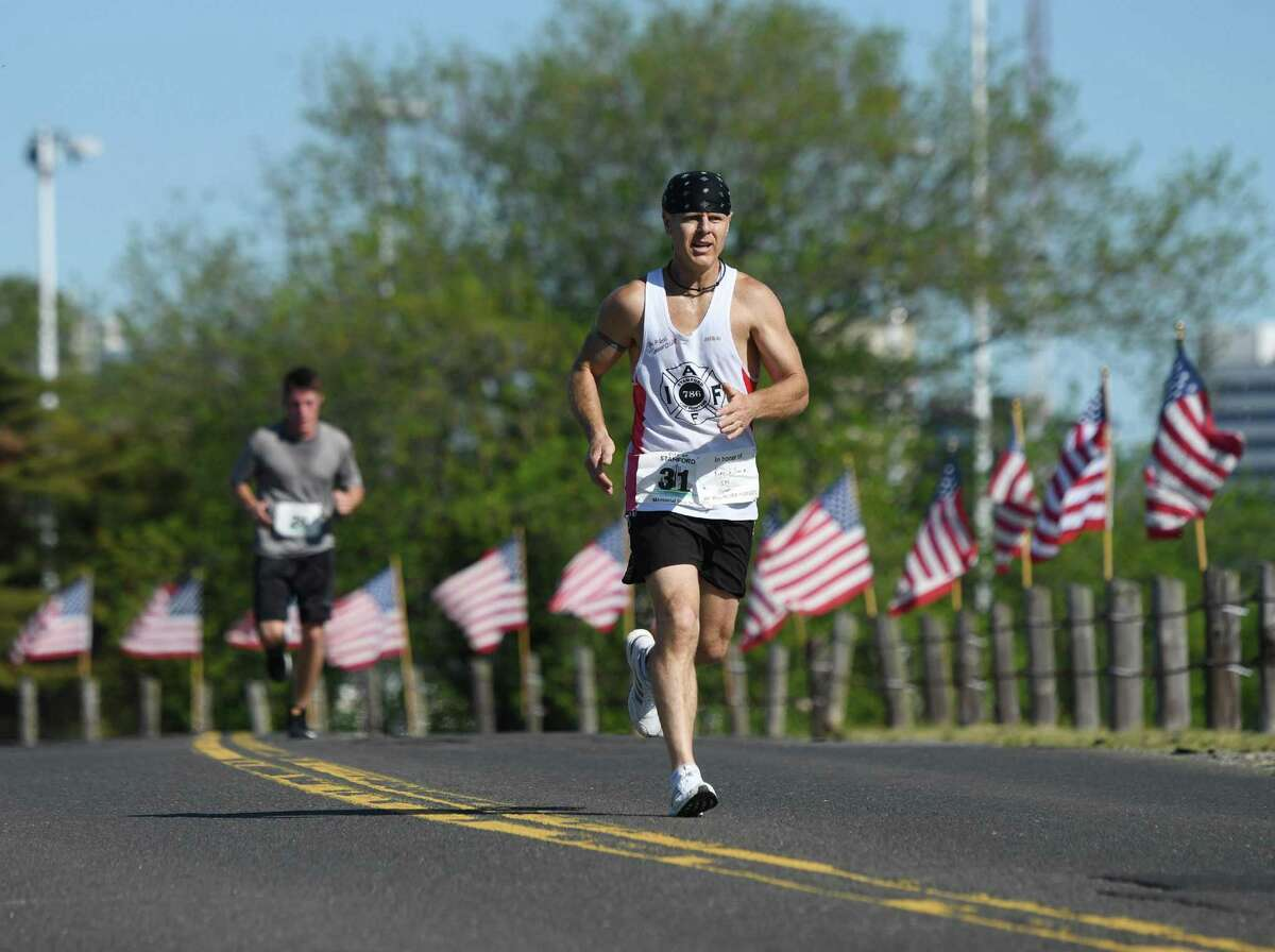 First-place finisher Al Hagander, of Darien, races down the home stretch in the first Memorial Day 5K run at Cummings Point Park in Stamford, Conn. Monday, May 27, 2019. Due to diminishing crowds and ongoing renovation of Veterans Memorial Park, Stamford held a 5K run and Memorial Day ceremony instead of the usual parade through downtown. About 300 runners participated in the 5K, which preceeded a service on the beach in honor of the fallen veterans.