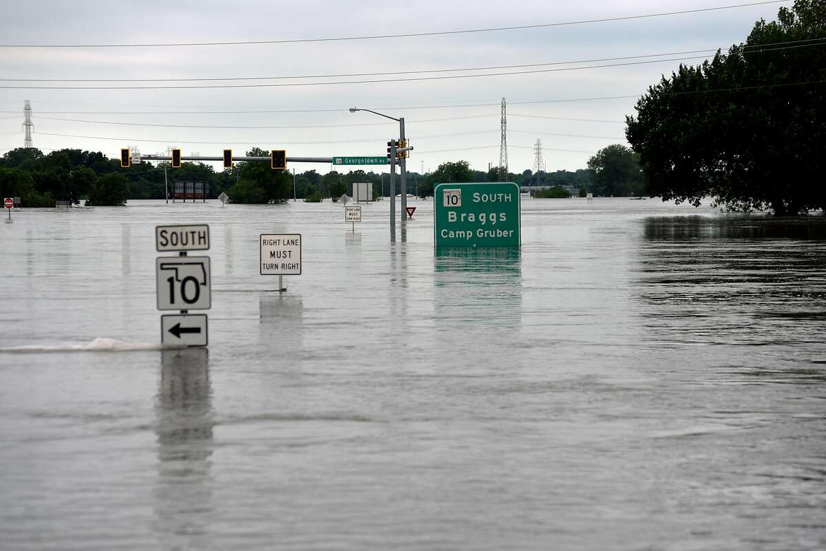 Floodwaters from the Arkansas River submerge roads Sunday in Fort Gibson, Okla. The river is cresting at record high levels with more rain on the way.