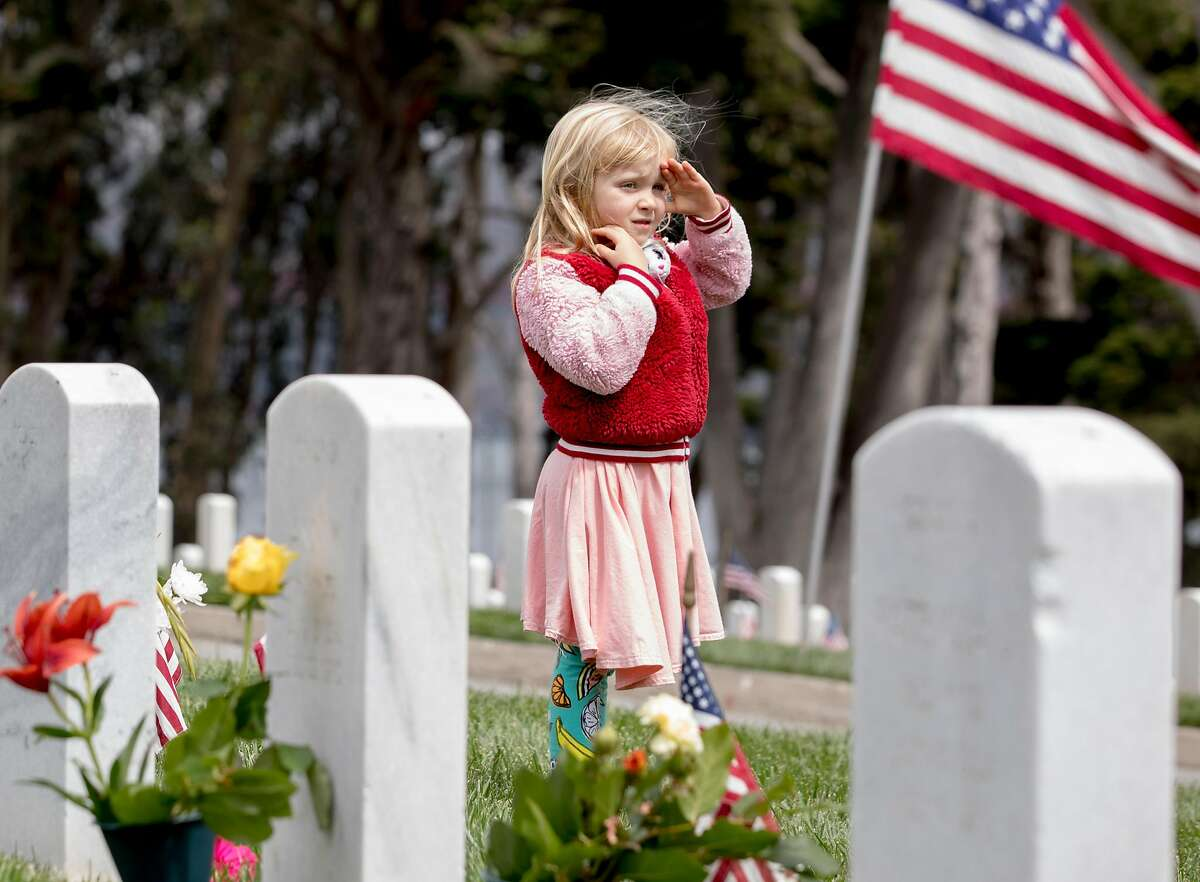 Evey Hillesheim, 6, of Pleasant Hill salutes a passing car carrying veterans during the annual Memorial Day observance held at the Presidio Cemetery in San Francisco, Calif. Monday, May 27, 2019.