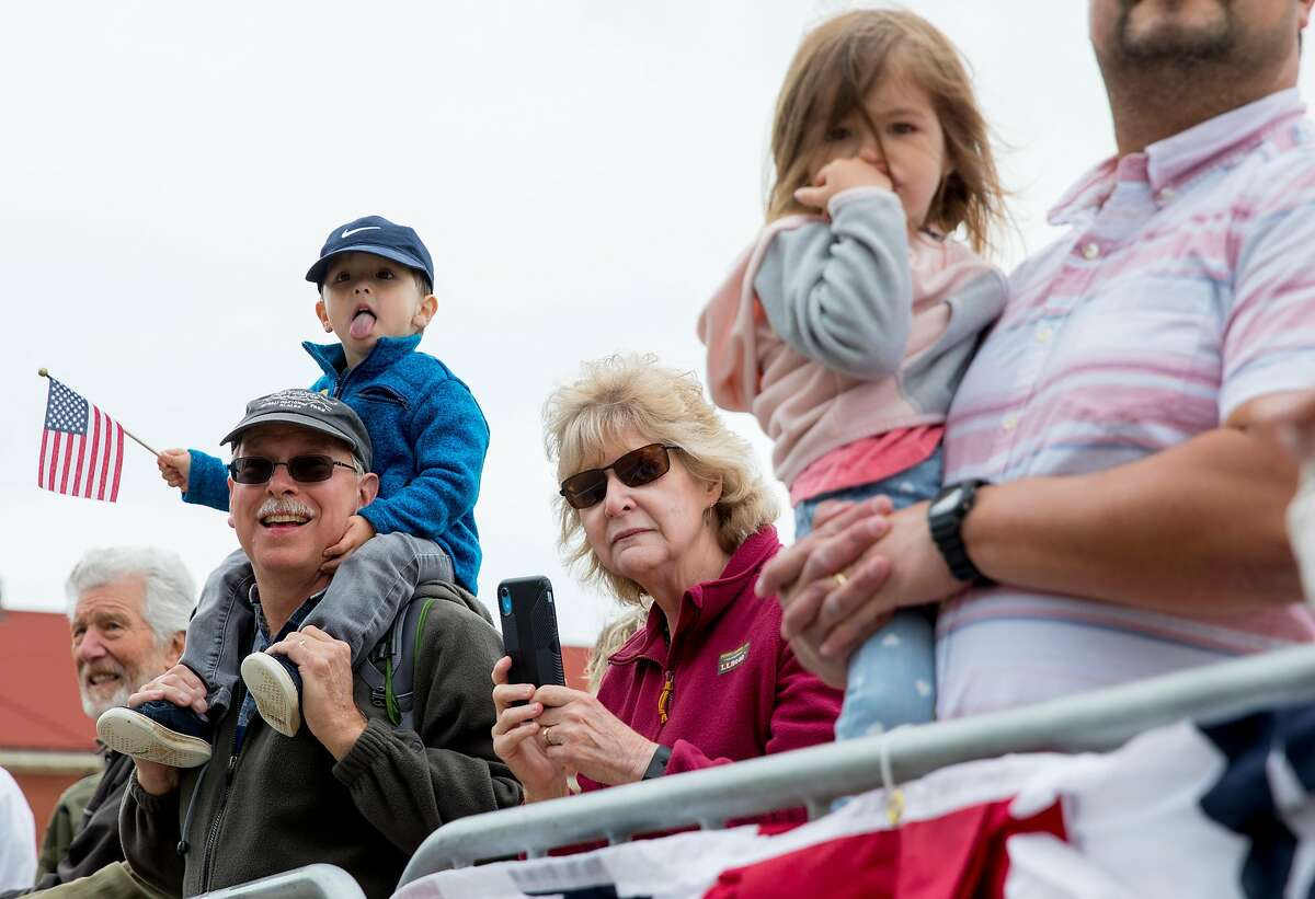 Spectators watch from the sidelines as a parade moves through the Presidio during the annual Memorial Day observance held at the Presidio Cemetery in San Francisco, Calif. Monday, May 27, 2019.