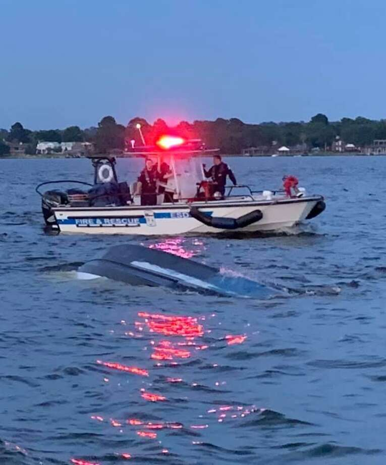 Montgomery County Precinct 1 Constable's deputies look on at a boat that capsized Sunday evening with 11 people in, including a baby. Photo: Courtesy Of The Montgomery County Precinct 1 Constable's Office