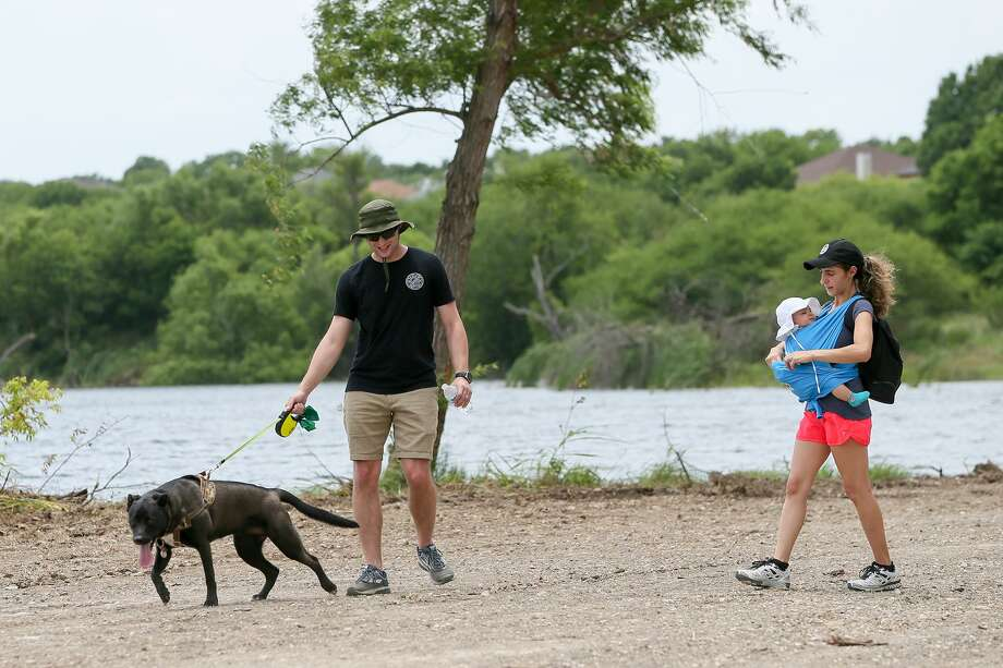 Christopher and Victoria Esposito walk their 4-month-old daughter, Lily, and their dog, Sierra, along the shore of City Park Lake in Converse following grand opening ceremonies for the lake on Friday. The city's public works department installed picnic tables, raised material around the shore, trimmed trees and moved mounds of dirt in the parking area to facilitate the opening of the lake. Work on refurbishing the park began early this year. Photo: Marvin Pfeiffer /Staff Photographer / Express-News 2019