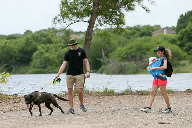 Christopher and Victoria Esposito walk their 4-month-old daughter, Lily, and their dog, Sierra, along the shore of City Park Lake in Converse following grand opening ceremonies for the lake on Friday. The city's public works department installed picnic tables, raised material around the shore, trimmed trees and moved mounds of dirt in the parking area to facilitate the opening of the lake. Work on refurbishing the park began early this year.