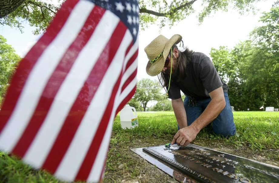 Matthew Sampson cleans Joseph Ira LeMaire Jr's memorial marker at Forest Lawn Memorial Park on Monday. Sampson started to clean veteran memorial markers after his friend United States Army Private First Class David Andrew Drake was killed in 2011 in Afghanistan. After cleaning Drake's and another's marker Sampson says he cleans different markers till he runs out of flags to place.  Photo taken on Monday, 05/27/19. Ryan Welch/The Enterprise Photo: Ryan Welch, Beuamont Enterprise / The Enterprise / © 2019 Beaumont Enterprise