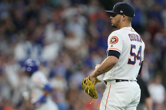 Houston Astros relief pitcher Roberto Osuna (54) reacts to Chicago Cubs shortstop Addison Russell (27) home-run during the 9th inning of an MLB baseball game at Minute Maid Park Monday, May 27, 2019, in Houston.