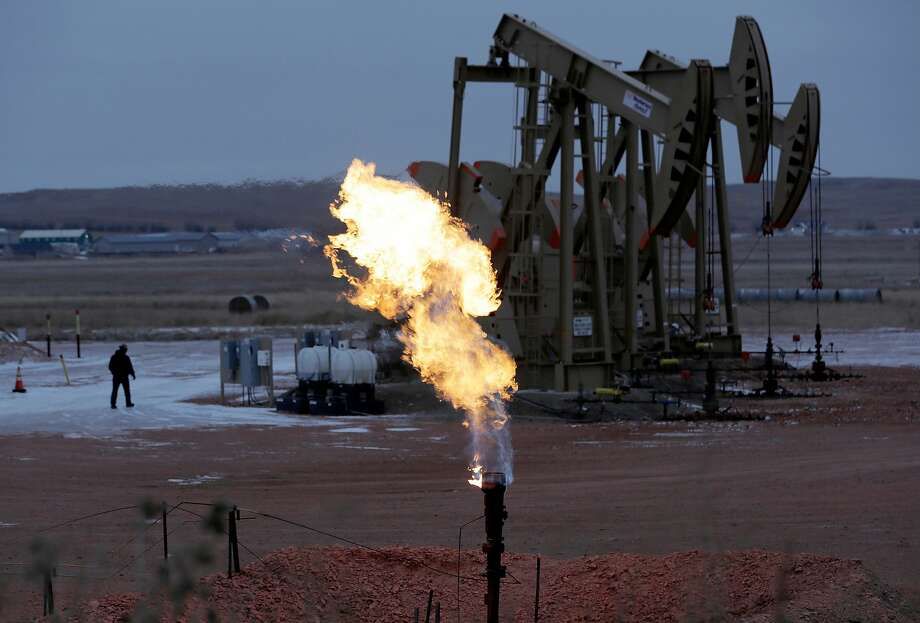 FILE - In this Oct. 22, 2015 file photo, workers tend to oil pump jacks behind a natural gas flare near Watford City, N.D.  Photo: Eric Gay, Associated Press
