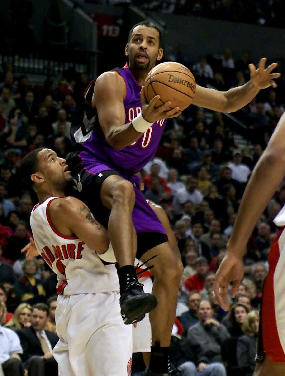 Toronto Raptors' Dell Curry lands on top of Trail Blazers' Damon Stoudamire as he drives to the hoop during their NBA game Wednesday, Dec. 6, 2000, in Portland, Ore.(AP Photo/Jack Smith)