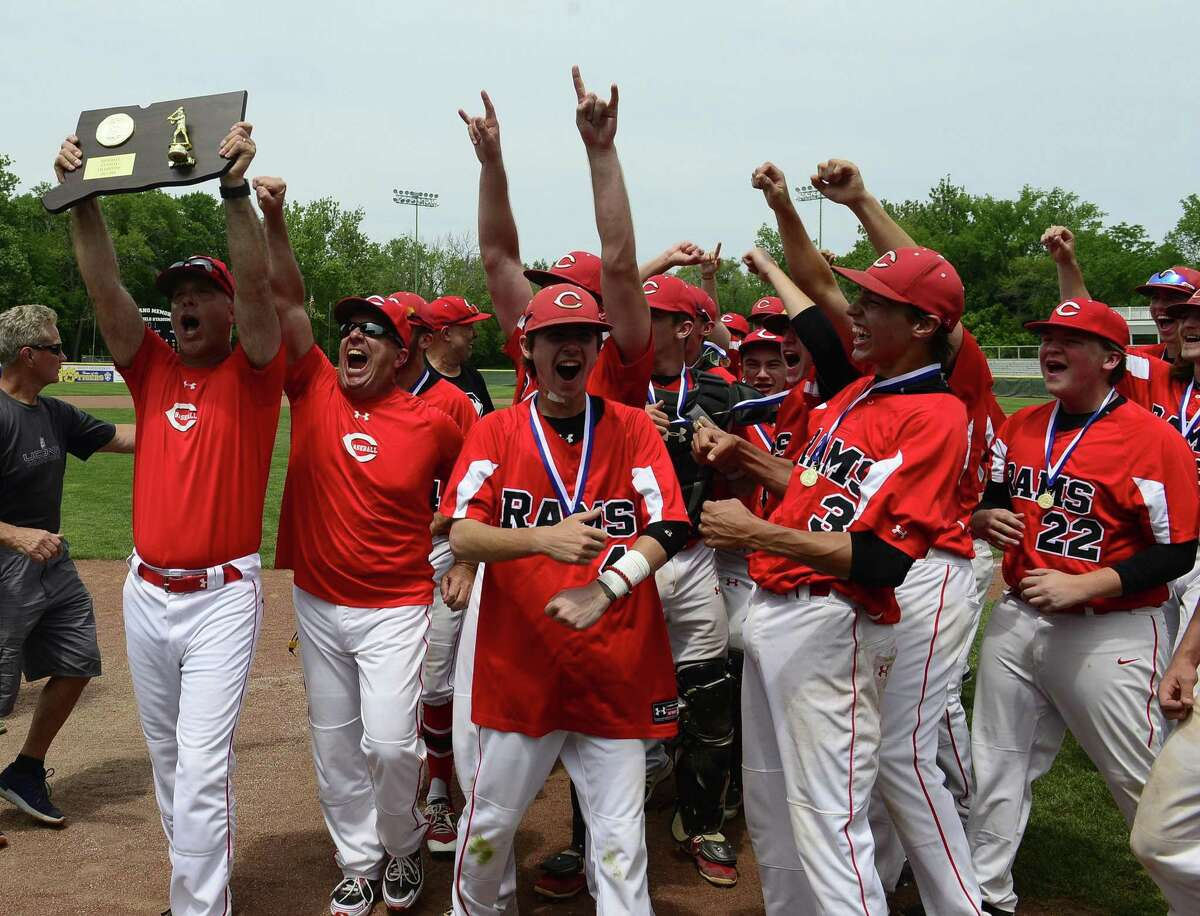Cheshire coach Bill Mrowka holds up the championship plaque as the Rams celebrate winning the CIAC Class LL baseball finals against Ridgefield at Palmer Field Stadium on June 9, 2018 in Middletown. Cheshire defeated Ridgefield 1-0.