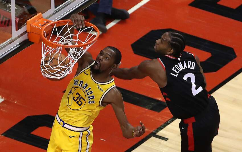 FILE - Golden State Warriors forward Kevin Durant (35) dunks after passing Toronto Raptors forward Kawhi Leonard (2) as the Toronto Raptors beat the Golden State Warriors 131-128 in overtime in Toronto. November 29, 2018.