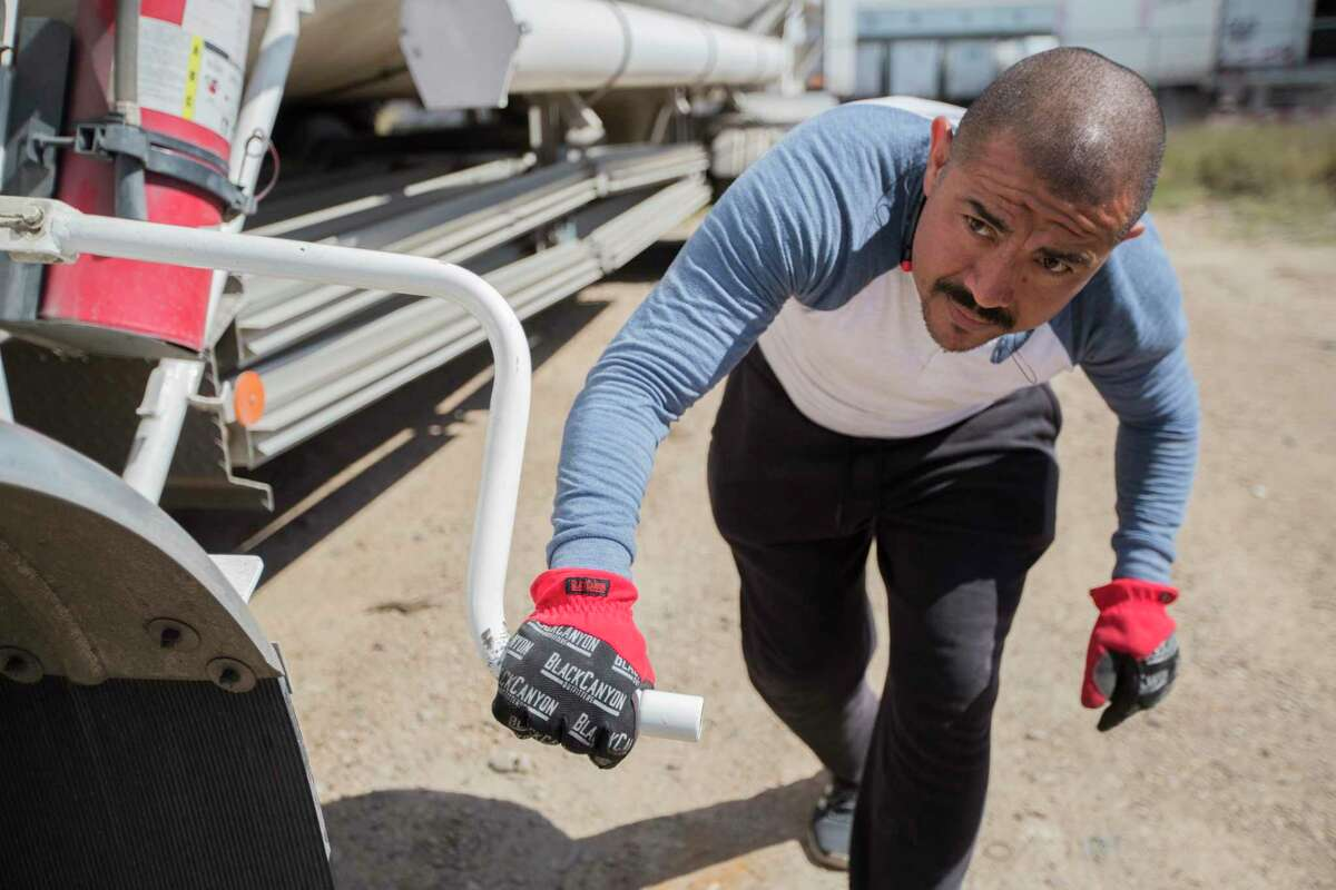A trucker attaches a tank with liquefied natural gas to later transport into a truck yard in Mexico.