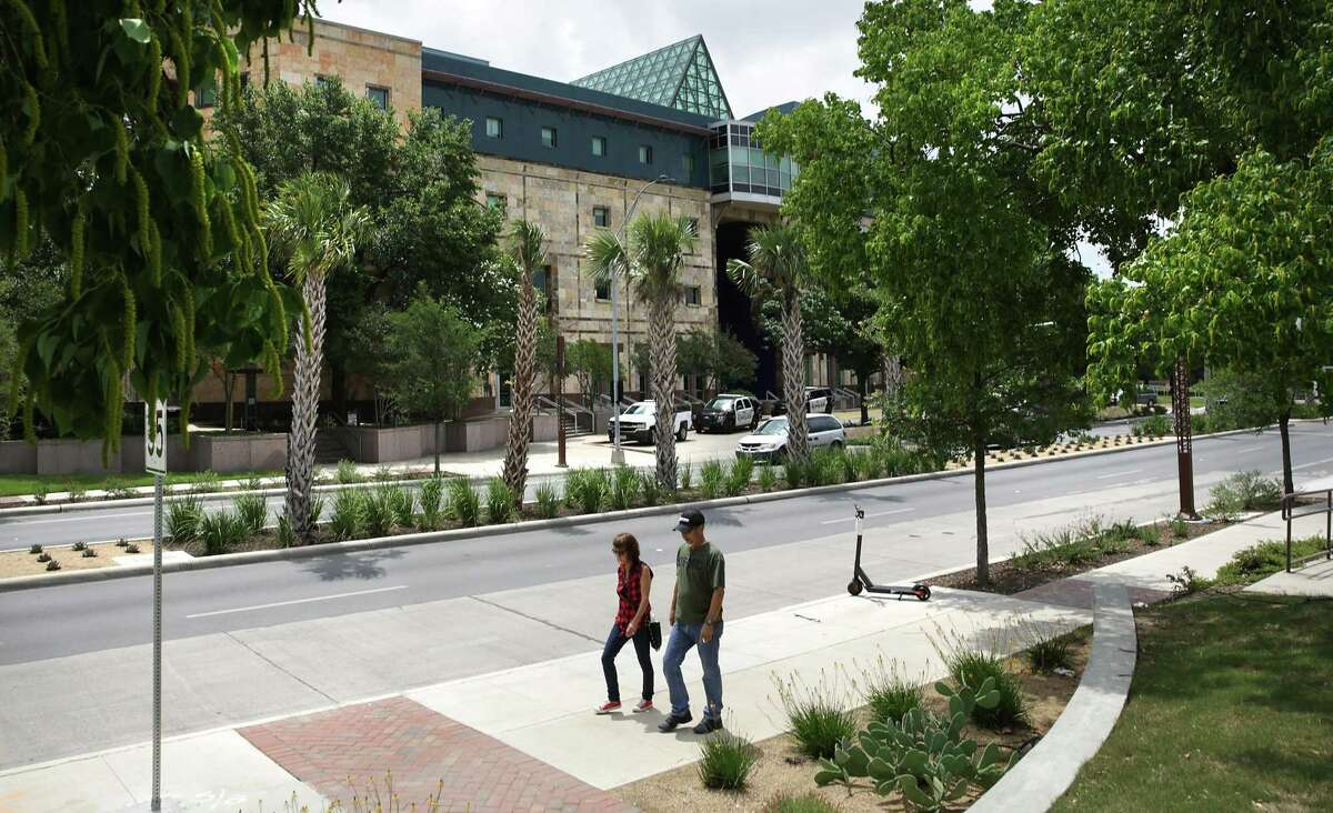 A couple walks past cacti, palms and other native plants on Frio Street at the UTSA downtown campus.