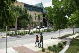 A couple walks past cacti, palms and other native plants that adorn the median of the remodeled Frio Street at the UTSA downtown campus.