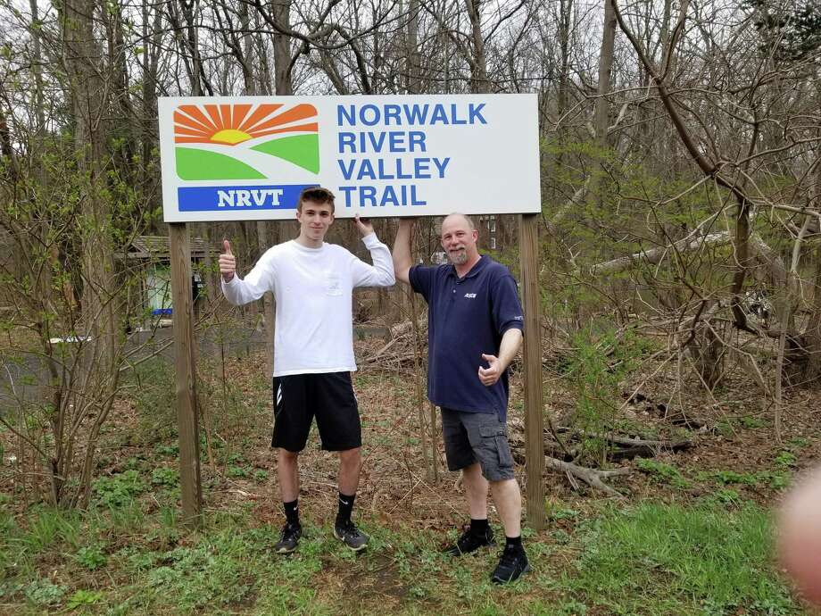 Boy Scout Colton Lovell, pictured with his father Mike, installed signage for the Norwalk River Valley Trail at Wolfpit Road and Route 7. Photo: Contributed Photo / Wilton Bulletin Contributed