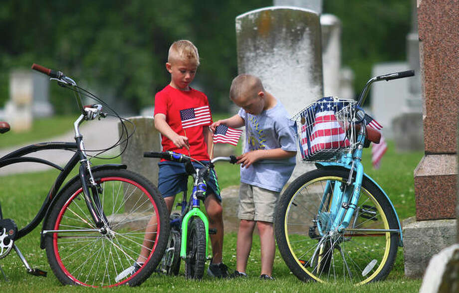 Grant Moore (left) and Tyler Andrews play with their bikes, which were decorated with flags for Memorial Day, after a ceremony at Winchester Cemetery Monday. Photo: Rosalind Essig | Journal-Courier