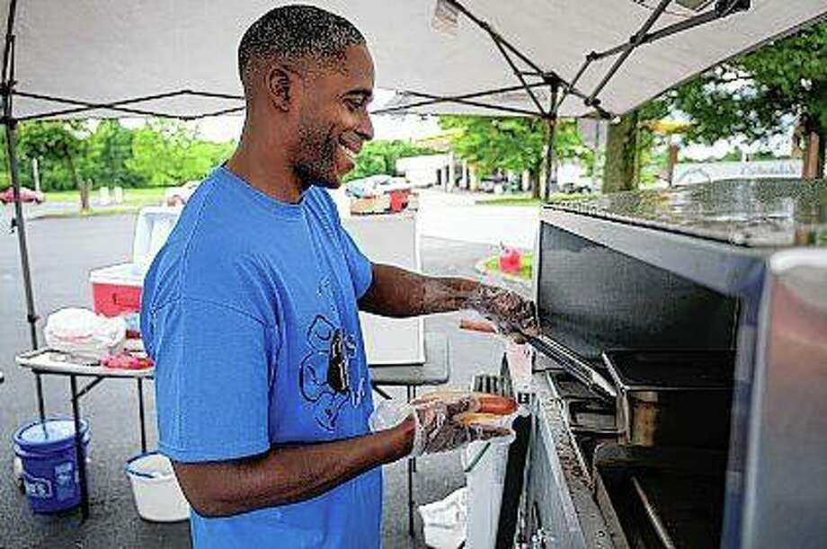 Solomon Muhammad prepares a hot dog at his cart in Carbondale. Solomon has overcome several obstacles, including two stints in prison, to turn his life around. Photo: Byron Hetzler | The Southern Illinoisan (AP)