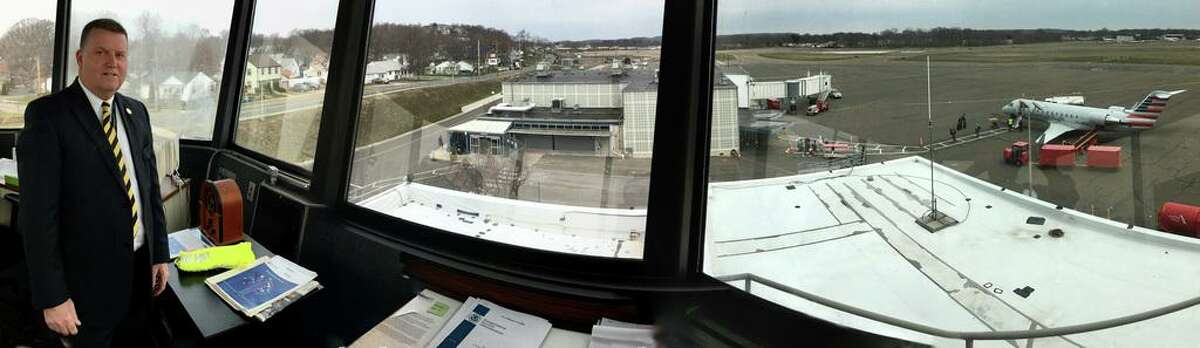 The view from the old tower at Tweed-New Haven Airport, showing an American Eagle 50-seat Bombardier aircraft unloading passengers, Timothy Larson, then a state senator and executive director of the Tweed airport authority, and houses directly across Burr Street.