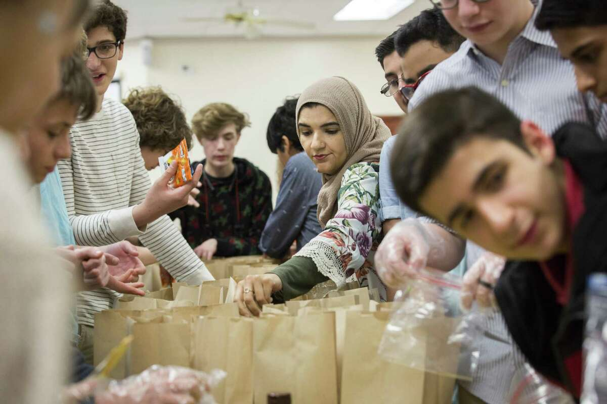 Surrounded by Muslim, Christian and Jewish teens, Sadia Jalali, 39, an ILM Academy counselor guides them on Sunday, May 19, 2019, in Houston, putting together snack bags to be taken to areas with people in need.