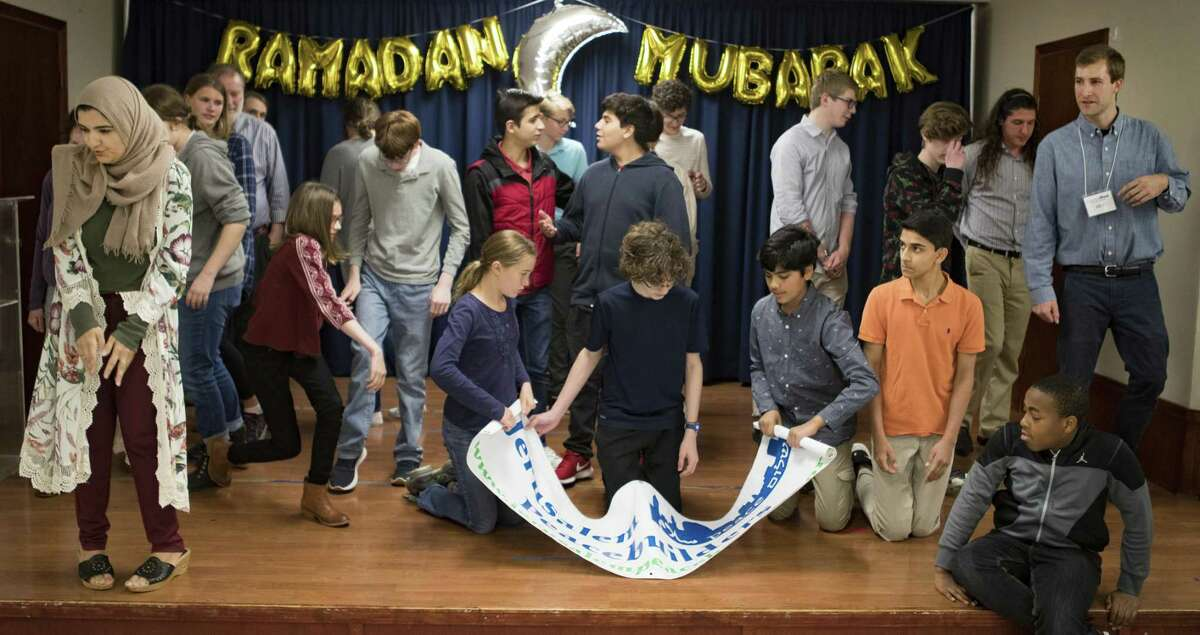 Muslim, Christian and Jewish teens get ready to take a class about Islam after a group photograph on Sunday, May 19, 2019, in Houston.