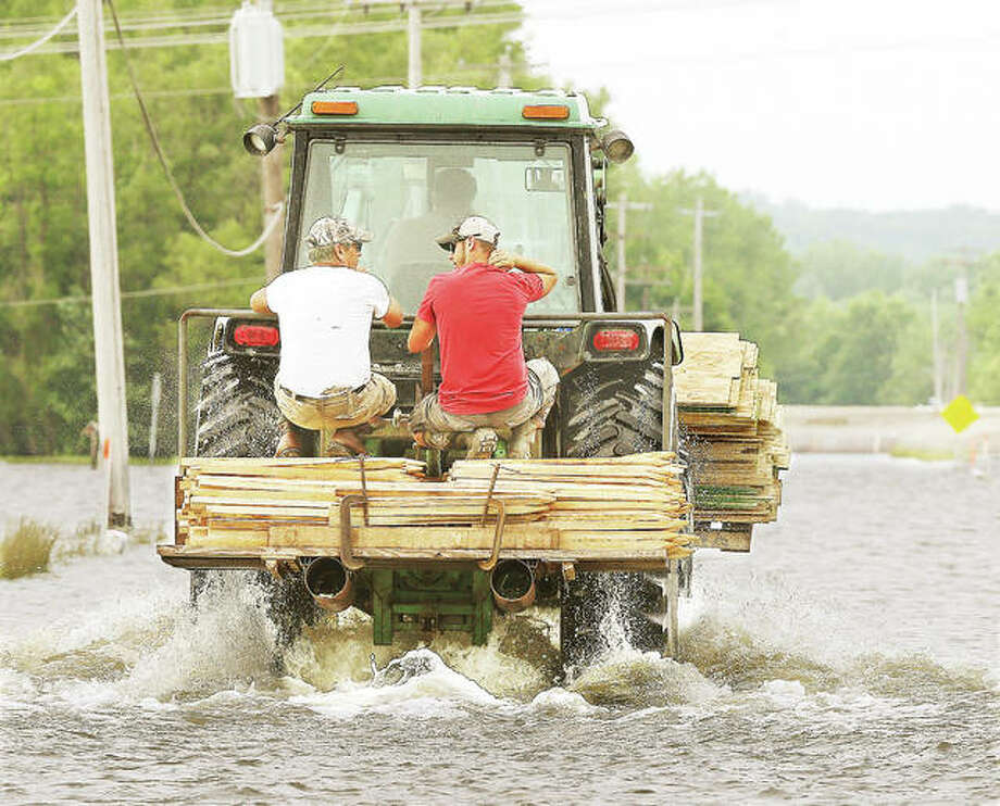 Two men ride out of West Alton, Missouri, with a load of plywood and timbers late Monday into the areas flooded to the north of town. Floodwaters were on Missouri Highway 94 at the northern edge of town and an intentional levee breach was planned for near the Riverlands late Monday evening.