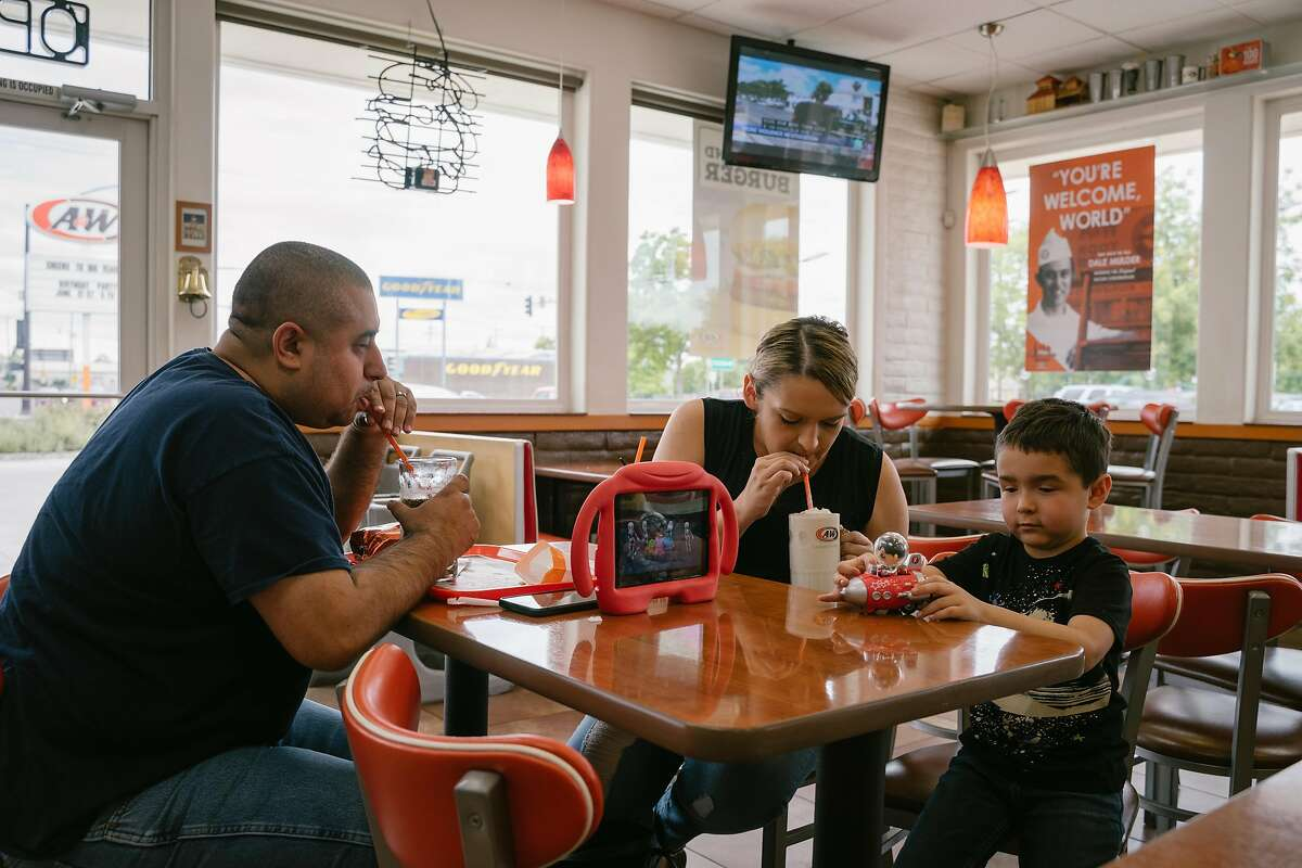 (Left) Tom and Amanda Becerra eat lunch with their son Oliver, 4, at A&W in Lodi, Calif., on Monday, May 27, 2019. The A&W franchise originally founded in Lodi, will be celebrating its 100th anniversary in June.
