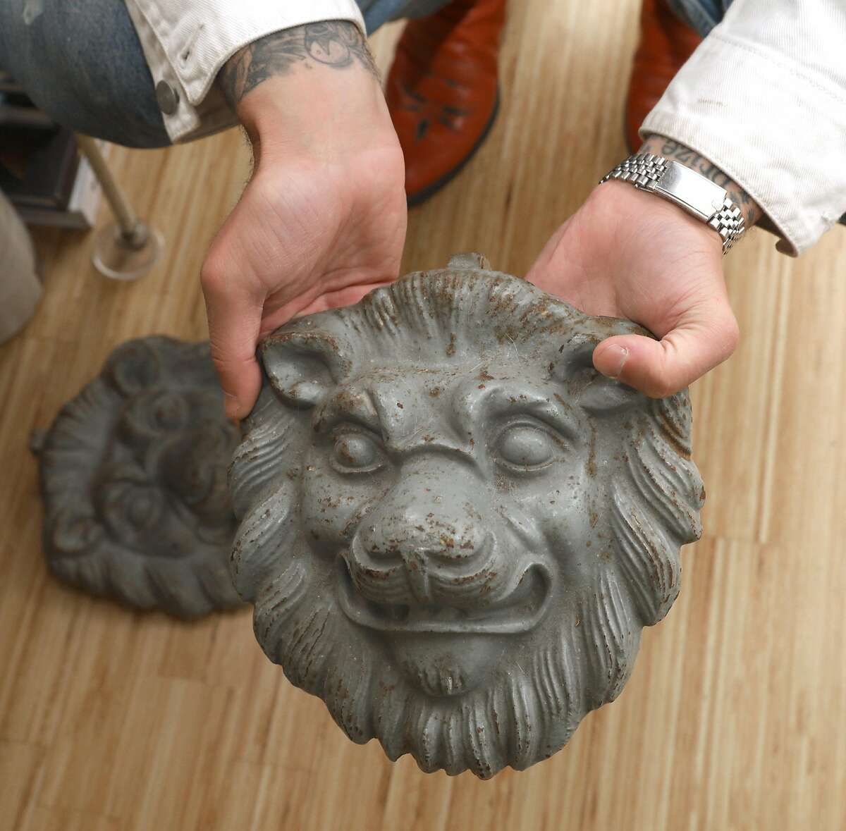 Josh Harris shows a pair of cast iron lion knockers picked up from Paris on Thursday, May 2, 2019, in San Francisco, Calif.