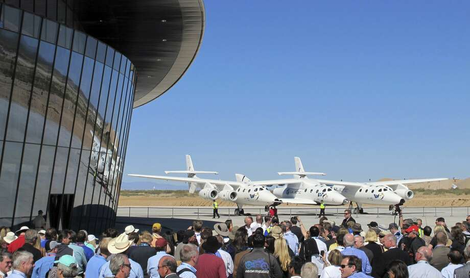 In this Oct. 17, 2011 photo a crowd gathers outside Spaceport America for a dedication ceremony as Virgin Galactic's custom-built jet aircraft WhiteKnightTwo and its spacecraft SpaceShipTwo sit on the tarmac near Upham, N.M. British billionaire Richard Branson is taking another concrete step toward offering rides into the close reaches of space for paying passengers. Branson announced Friday, May 10, 2019, that Virgin Galactic will immediately begin shifting operations from California to a spaceport and specialized runway in the New Mexico desert in final preparations for commercial flights. He says Virgin Galactic's development and testing program has advanced enough to make the move, which will continue through the summer. (Associated Press)