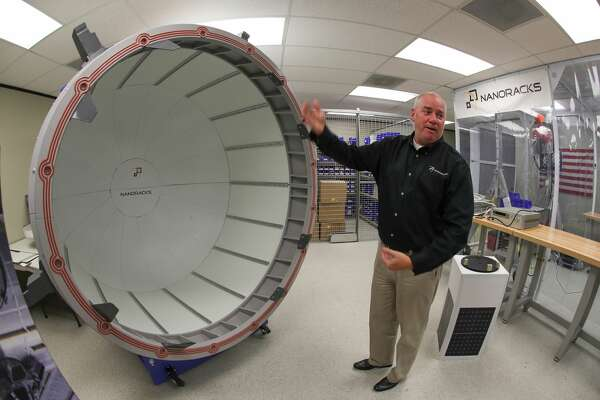 NanoRacks Project Manager Brock Howe uses a  full scale model to demonstrate how their commercial airlock system will work on the International Space Station Tuesday, July 25, 2017, in Webster.