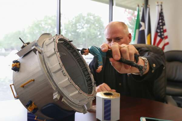 NanoRacks Project Manager Brock Howe uses a model with an action figure to demonstrate how their commercial airlock system will work on the International Space Station Tuesday, July 25, 2017, in Webster.
