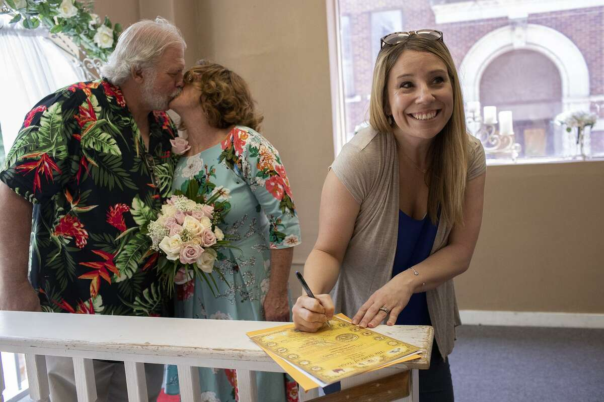 Sheila Aylor signs the marriage license as a witness for the marriage of Vickey Gauwitz and Steve Baker, left, as they kiss for a camera held by the officiant, Rev. Don Lang, (not pictured) before their wedding at the Courthouse Wedding Chapel in San Antonio on Friday, May 24, 2019.