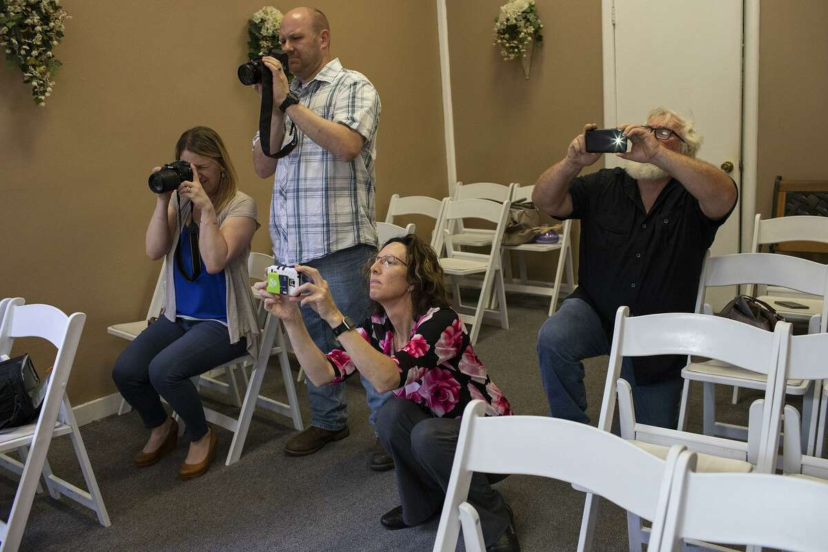 Sheila Aylor, from left, Nick Aylor, Alicia Thompson and Roy Gauwitz photograph the wedding of Vickey Gauwitz and Steve Baker at the Courthouse Wedding Chapel in San Antonio on Friday, May 24, 2019.