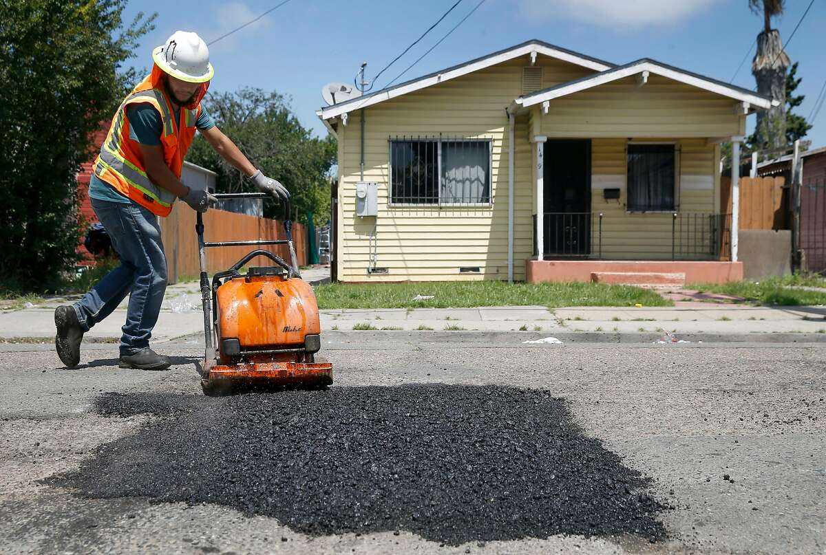 Roberto Hernandez from the Streets and Sidewalks department fills a pothole on 81st Avenue east of International Boulevard in Oakland, Calif. on Tuesday, May 28, 2019. Residents on the block said the potholes have been a problem for two years.