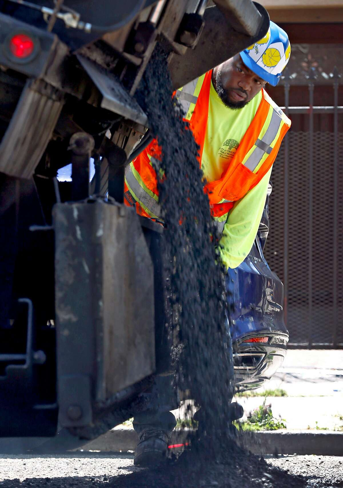 David Randolph pours asphalt onto the road as a maintenance crew from the Streets and Sidewalks department repairs potholes on 81st Avenue east of International Boulevard in Oakland, Calif. on Tuesday, May 28, 2019. Residents on the block said the potholes have been a problem for two years.