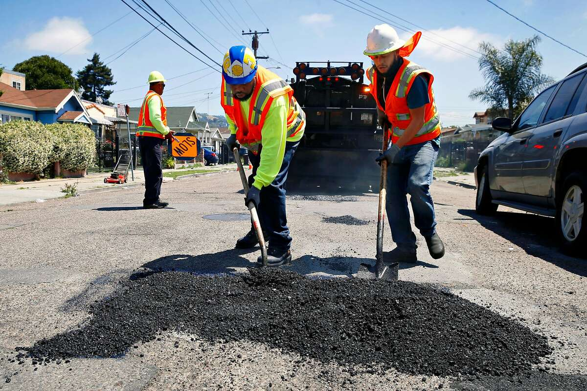 David Randolph (left) and Roberto Hernandez from the Streets and Sidewalks department repair potholes on 81st Avenue east of International Boulevard in Oakland, Calif. on Tuesday, May 28, 2019. Residents on the block said the potholes have been a problem for two years.