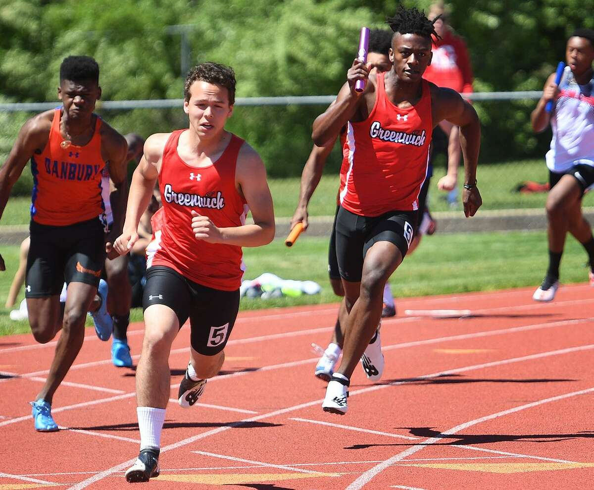 Greenwich's Zane Nye is ready to receive the baton from teammate Ryan Raybuck, right, on their way to winning the 4x100-meter relay at the FCIAC Outdoor Track and Field Championships on May 21 at Southern Connecticut State University in New Haven.