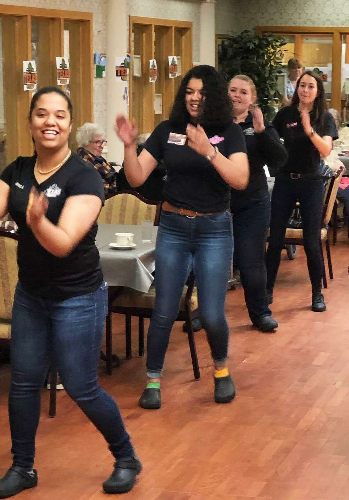 Servers from the Danbury Texas Roadhouse, from front to back, Manuela Aleman, Raquel Howard Kaitlyn O'Hara and Mikayla Ramos, kick off lunch with line dancing.