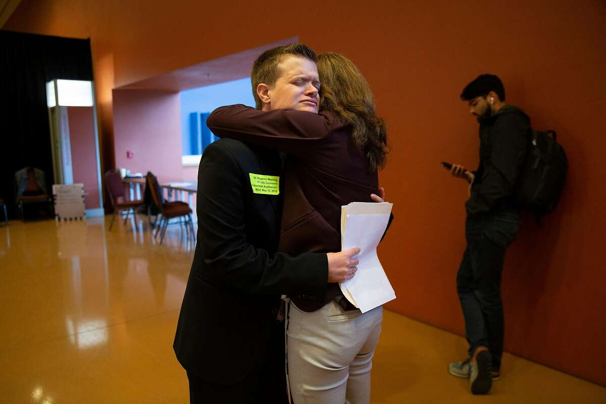 From left: Evan Minton and Amy Brown embrace after Minton addressed the UC Board of Regents during public comment at their regents meeting at UCSF Mission Bay on Wednesday, May 15, 2019, in San Francisco, Calif. The regents listened from supporters and opponents of a proposed partnership between UCSF and a Catholic hospital system that does not perform certain operations because of religious beliefs. Minton is transgender man who said he was refused a hysterectomy by a Dignity Health hospital. Brown is a supporter of Minton.