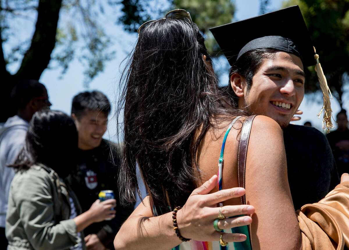 Jirayut New Latthivongskorn hugs a high school friend while wearing his graduation cap during his graduation party held at Marina Park in San Leandro, Calif. Saturday, May 25, 2019. Latthivongskorn is the first undocumented immigrant to graduate from UCSF's School of Medicine.