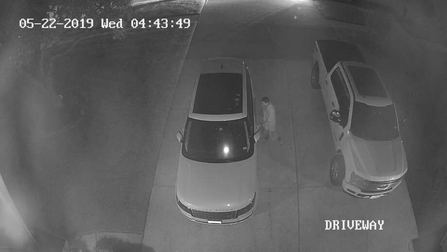 This still image from a surveillance video shows a man allegedly trying to break into a vehicle in a home's driveway. Photo: Courtesy Of The Montgomery County Constable's Office
