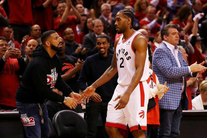 Kawhi Leonard of the Toronto Raptors high fives rapper Drake during game four of the NBA Eastern Conference Finals between the Milwaukee Bucks and the Toronto Raptors at Scotiabank Arena on May 21, 2019.