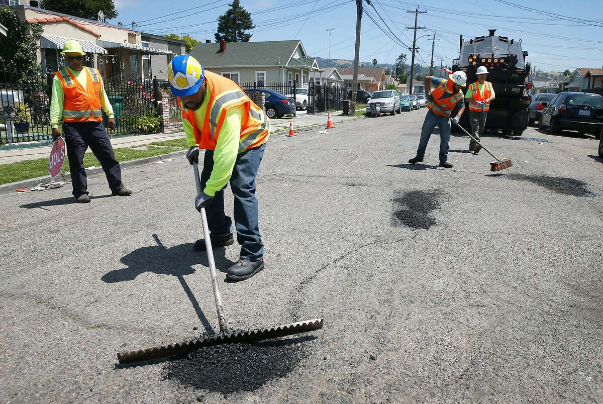 FILE - A maintenance crew from the Streets and Sidewalks department repairs potholes on 81st Avenue east of International Boulevard in Oakland, Calif. on Tuesday, May 28, 2019. Residents on the block said the potholes have been a problem for two years. Harold Street was recently repaved as part of the city's three-year pavement plan.