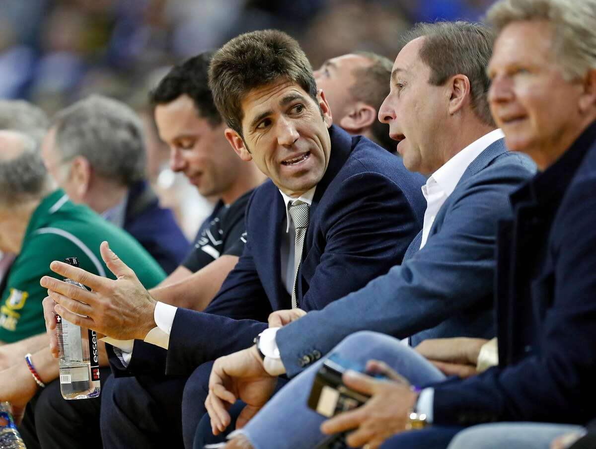 Golden State Warriors' Bob Myers talks with Joe Lacob while Warriors play Detroit Pistons during NBA game at Oracle Arena in Oakland, Calif., on Sunday, March 24, 2019.