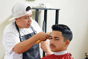 Mario Camargo cuts the hair of Isaac Garza on Wednesday night at Fades & Blades Barber Shop in Plainview. Camargo stayed late on Wednesday to service clients after returning from the Connecticut Barber Expo last weekend.
