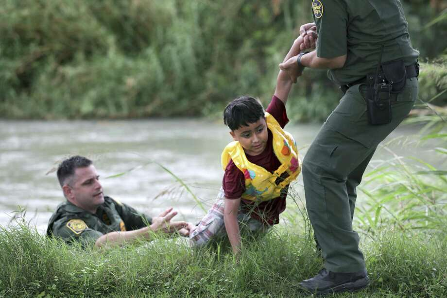 In this 2019 file photo, a Border Patrol agent in Eagle Pass rescues a 7-year-old Honduran from the Rio Grande near Eagle Pass, Texas. Photo: Bob Owen /Associated Press / ©2019 San Antonio Express-News